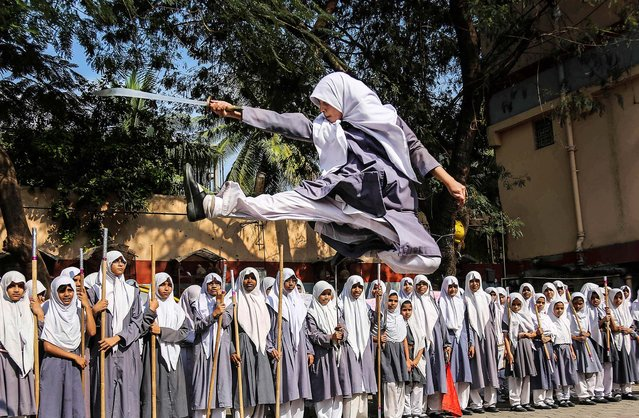 A girl performs martial arts during a function to mark International Women's Day at a school in Hyderabad, India, on March 7, 2014. (Photo by Mahesh Kumar A./Associated Press)