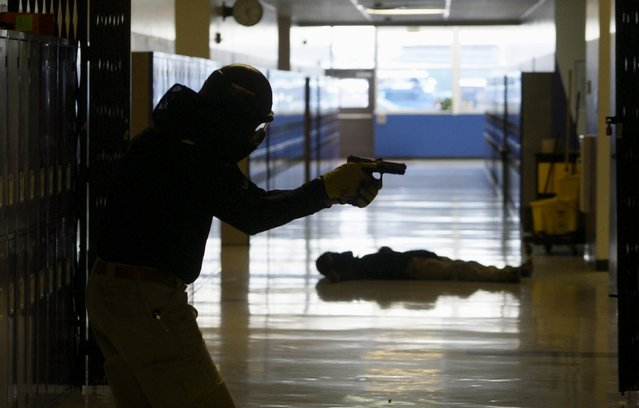 A student searches for a shooter with a mock victim in the background in a middle school during an Active Shooter Response course offered by TAC ONE Consulting in Denver April 2, 2016. (Photo by Rick Wilking/Reuters)
