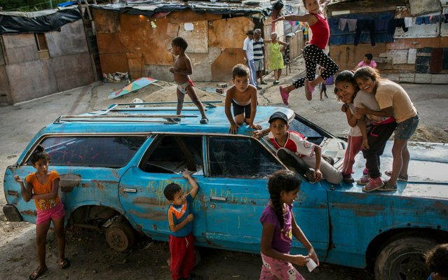 "Children play on top of an abandoned car at the ""Aguerridos Liberator"" shanty town in Caracas, Venezuela, Thursday, May 9, 2019. (Photo by Rodrigo Abd/AP Photo)"