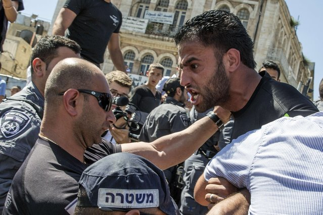 """Palestinian demonstrators are confronted by Israeli police during the Israeli's """"flag march"""" through Damascus Gate in Jerusalem's old city during celebrations for Jerusalem Day on May 17, 2015 which marks the anniversary of the """"reunification"""" of the holy city after Israel captured the Arab eastern sector from Jordan during the 1967 Six-Day War. (Photo by Jack Guez/AFP Photo)"""