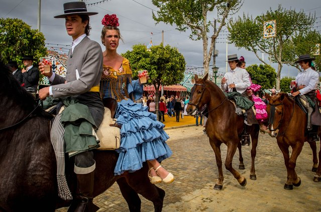 Participants in traditional dress ride on horseback as they enjoy the atmosphere at the Feria de Abril (April's Fair) on April 12, 2016 in Seville, Spain. The Feria de Abril has a history that dates back to 1857 and takes place a fortnight after Easter each year. The origin of the fair was a cattle market but the event quickly turned its goal from commerce to having fun. More than 1 million local and international participants are expected to attend the Feria de Abril. (Photo by David Ramos/Getty Images)