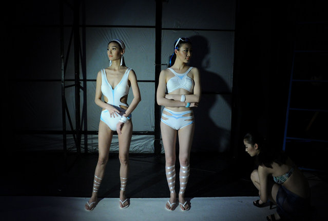 Models get ready backstage before the Hosa Swimming Fashion Trend Show during China Fashion Week in Beijing on March 28, 2014. (Photo by Wang Zhao/AFP Photo)