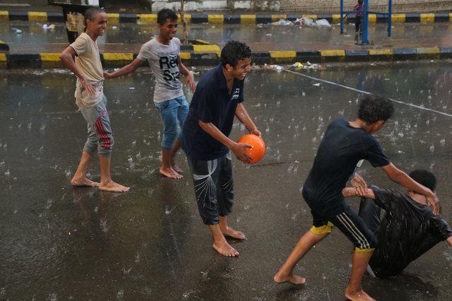 Yemen youths play soccer in the rain on a street in Taiz city, Yemen, Sunday, May 17, 2015. (Photo by Abdulnasser Alseddik/AP Photo)