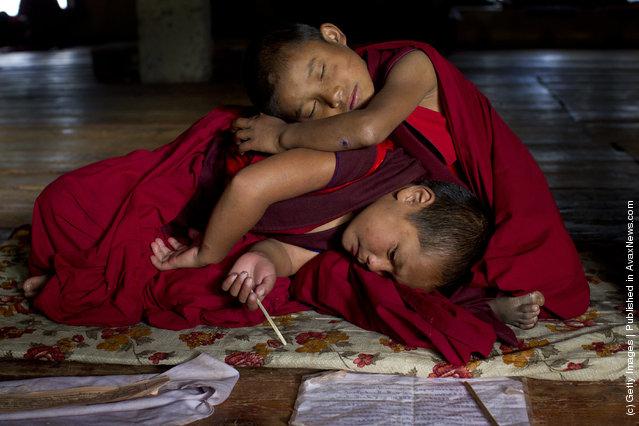 Sangey, 6, and Tenzin, 7, rest after hours of prayer at the Dechen Phodrang monastery in Thimphu, Bhutan