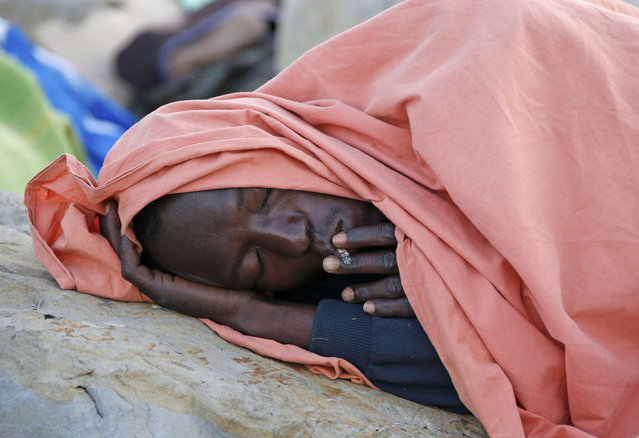A migrant smokes as he rests under a blanket on the rocks of the seawall at the Saint Ludovic border crossing on the Mediterranean Sea between Vintimille, Italy and Menton, France, June 17, 2015. Police on Tuesday began hauling away mostly African migrants from makeshift camps on the Italy-France border as European Union ministers met in Luxembourg to hash out plans to deal with the immigration crisis.   REUTERS/Eric Gaillard