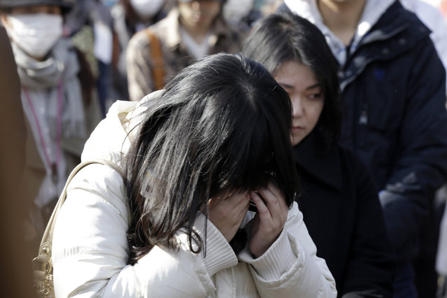 A woman cries as she mourns the victims of the March 11, 2011 earthquake and tsunami during a special memorial event in Tokyo, Saturday, March 11, 2017. Japan on Saturday marked the sixth anniversary of the 2011 tsunami that killed more than 18,000 people and left a devastated coastline along the country's northeast that has still not been fully rebuilt. (Photo by Eugene Hoshiko/AP Photo)