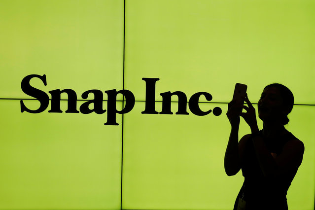 A woman stands in front of the logo of Snap Inc. on the floor of the New York Stock Exchange (NYSE) while waiting for Snap Inc. to post their IPO, in New York City, NY, U.S. March 2, 2017. (Photo by Lucas Jackson/Reuters)