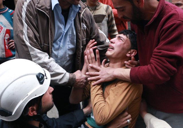 A man is comforted by a rescue worker and others following a reported air strike by government forces in which a fellow rescue worker was killed on March 8, 2014 in the northern city of Aleppo. More than 140,000 people have been killed in Syria since the start of a March 2011 uprising against the Assad family's 40-year rule. (Photo by Fadi Al-Halabi/AFP Photo/AMC)