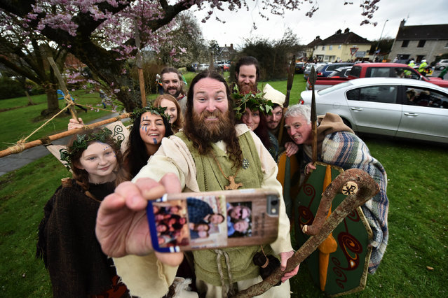 Saint Patrick, played by actor Marty Burns takes a selfie along with members of the Magnus Vikings Association before they part in the cross community Saint Patrick's Day parade on March 17, 2017 in Downpatrick, Northern Ireland. Tradition holds that Saint Patrick and his companions landed at the mouth of the Slaney river, a few miles from Down Cathedral, in 432 AD. From here Patrick travelled extensively spreading the teachings of Christianity before his death on 17th March 461 AD. He is buried at nearby Down Cathedral. (Photo by Charles McQuillan/Getty Images)