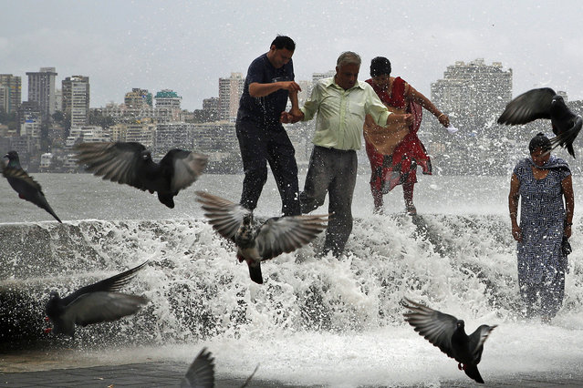 Indians try to walk away as huge tidal waves hit the Arabian Sea shore marking the arrival of monsoon season in Mumbai, India, Tuesday, June 16, 2015. The annual monsoon rains which usually hit India from June to September are crucial for farmers whose crops feed hundreds of millions of people. (Photo by Rajanish Kakade/AP Photo)