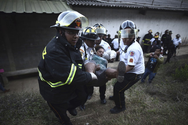 Firefighters carry a woman who fainted outside a reformatory for youth and men, Centro Correccional Etapa II, where a riot and fire broke out in San Jose Pinula, Guatemala, Sunday, March 19, 2017. At least one man died, a jail monitor, during the riot, according the police spokesman Pablo Castillo. (Photo by Oliver de Ros/AP Photo)