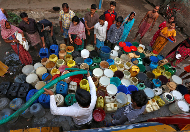 Residents wait as they get their containers filled with drinking water from a municipal tanker at a slum in Kolkata, March 22, 2017. (Photo by Rupak De Chowdhuri/Reuters)