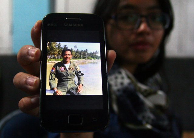 A relative in Malang holds up her smartphone showing a photograph of Indonesian Air Force captain Sandy Permana, who was a crew member aboard the Indonesian Air Force C-130 Hercules aircraft that crashed in Medan, northern Sumatra on June 30, 2015. (Photo by Aman Rochman/AFP Photo)