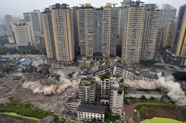 Old residential buildings are demolished with controlled blasting in Chongqing municipality, China, June 16, 2015. (Photo by Reuters/China Daily)