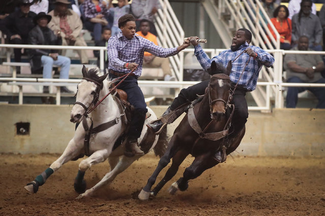Cowboys hand off the baton in the relay race competition at the Bill Pickett Invitational Rodeo on April 1, 2017 in Memphis, Tennessee. (Photo by Scott Olson/Getty Images)