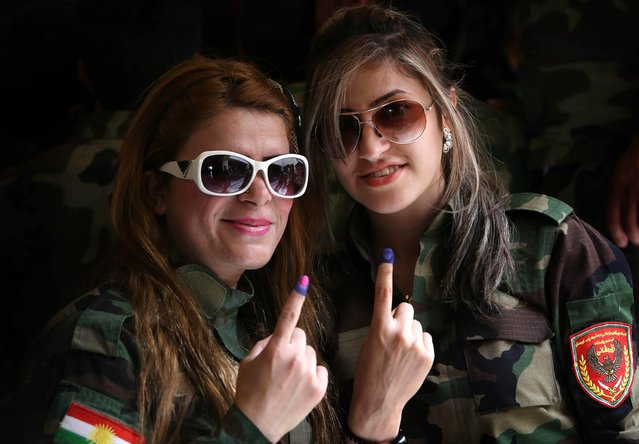 Members of the Kurdish Peshmerga force show their ink-stained fingers in the northern Kurdish city of Arbil on April 28, 2014, after casting her ballot in special voting ahead of Iraq's first election since US troops withdrew. Suicide bombers attacked several polling stations and security forces in Iraq today killing at least 18 people and wounding dozens, police said, days before the violence-wracked country holds legislative elections. (Photo by Safin Hamed/AFP Photo)