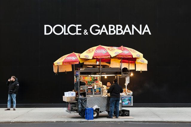 A hotdog vendor talks to a customer next to a future Dolce & Gabbana store on 5th Avenue in New York, February 26, 2012. (Photo by Natan Dvir/Polaris)