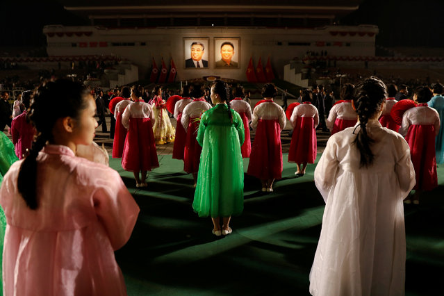 Portraits of North Korea founder Kim Il Sung and late leader Kim Jong Il glow as people take part in a mass dance event marking the 105th birth anniversary of Kim Il Sung in Pyongyang, North Korea April 15, 2017. (Photo by Damir Sagolj/Reuters)