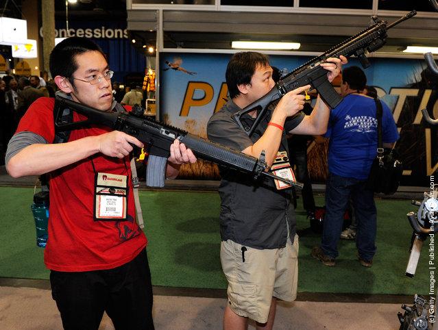 Wayne Tran (L) and Chris Nguyen, both of California, look at SIG556 semi-automatic rifles at the Sig Sauer booth