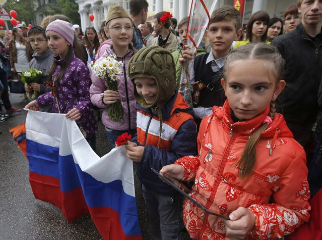 Children hold a Russian flag as they take part in celebrations to mark Victory day in the Crimean port of Sevastopol May 9, 2014. (Photo by Maxim Shemetov/Reuters)