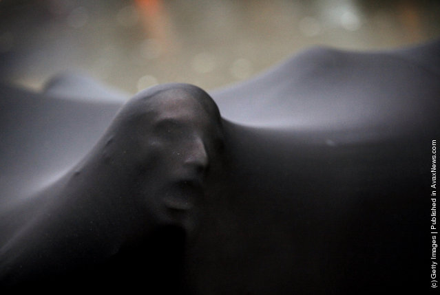 The amorphous black blob, a group of performers huddled underneath stretched black material, makes its way among the Occupy Wall Street West protests in the financial district
