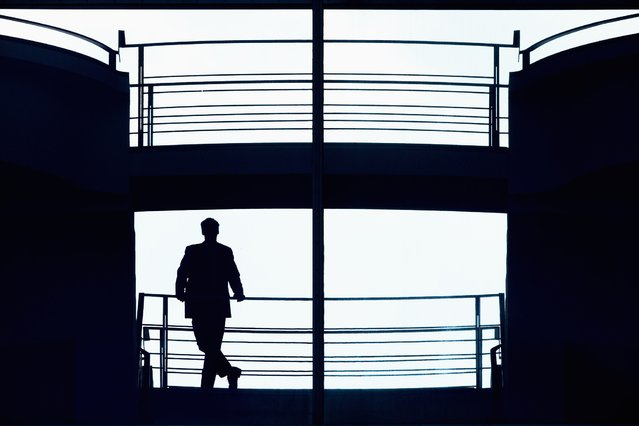 A man is silhouetted as he stands on a walkway in the sky lobby at the Chancellery, the seat of German Chancellor Angela Merkel (not pictured) in Berlin, May 7, 2014. (Photo by Thomas Peter/Reuters)