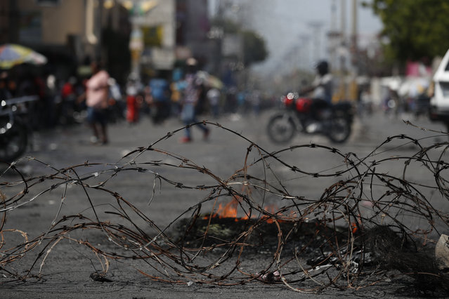 People walk and drive motorcycles past a barricade of barbed wire and the remains of burning tires, set up by anti-government protesters who are trying to paralyze transport and commerce to pressure President Jovenel Moise to resign, in Port-au-Prince, Haiti, Tuesday, October 8, 2019. (Photo by Rebecca Blackwell/AP Photo)