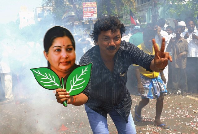 A supporter holds up a placard bearing the portrait of southern Indian state of Tamil Nadu Chief Minister and General Secretary of The All India Anna Dravida Munnetra Kazhagam (AIADMK) Party J. Jayalalithaa during celebrations in Chennai on May 16, 2014. (Photo by AFP Photo/STR)