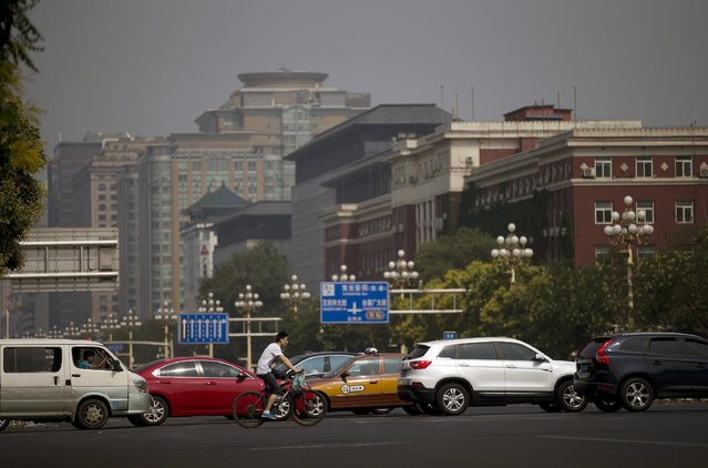 A cyclist rides past  busy traffic and government administrative buildings on Chang'an Avenue in Beijing Sunday, July 12, 2015. Beijing's city government said Sunday that it is going to move part of its administrative functions out of the city center as part of a plan to better integrate the Chinese capital with its surrounding areas. (Photo by Andy Wong/AP Photo)