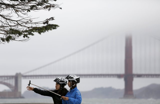 A woman adjusts a mobile device before taking a photograph in San Francisco, California, July 21, 2015. (Photo by Robert Galbraith/Reuters)