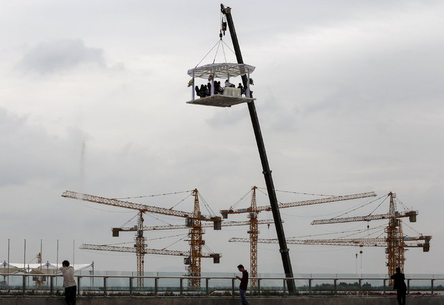 Bystanders look on as people dine at a table lifted by a crane to a height of 30 metres mid-air, near a residential construction site, in Kunming, Yunnan province, China, July 23, 2015. According to local media, having a meal at this lifted dining table can cost 8,888 yuan (1,431 USD) for one person. (Photo by Wong Campion/Reuters)