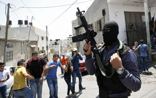 A Palestinian militant takes part in the funeral of Palestinian Mohammed Abu Latifa, 19, in Qalandiya refugee camp, near the West Bank city of Ramallah July 27, 2015. Abu Latifa, wanted on suspicion of planning a militant attack, fell to his death from a rooftop on Monday as he fled from police in the occupied West Bank, Israeli police said, an account disputed by a witness. (Photo by Mohamad Torokman/Reuters)