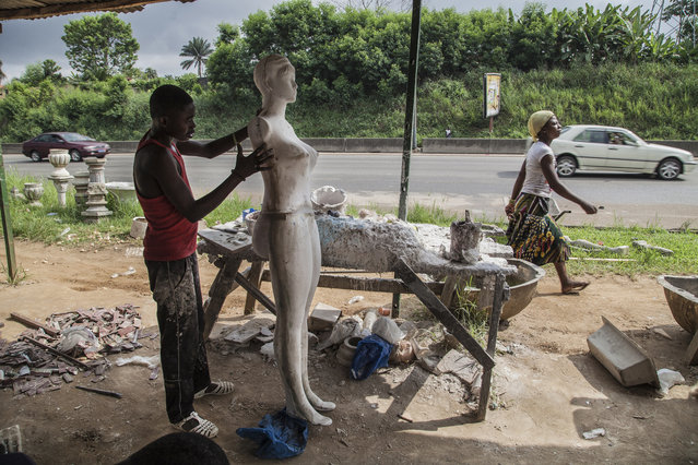 In Ivorian popular culture, Awoulabas are beautiful women with large breasts and, above all, big buttocks. Here: An apprentice polishes a mannequin. Each one usually takes a week to complete. (Photo by Joana Choumali)