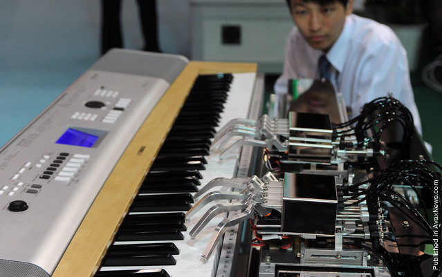A man watches a piano-playing robot in action during the Taipei International Robot Show on October 19, 2010. Some 300 exhibitors from 66 companies took part in the four-day exhibition