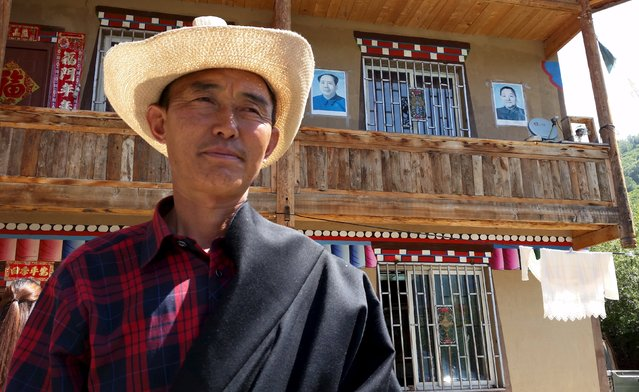 A guest house owner poses in front of his property with posters of China's late Chairman Mao Zedong and leader Deng Xiaoping on the wall, in Aba Tibetan and Qiang Autonomous Prefecture, Sichuan province, July 30, 2015. (Photo by Natalie Thomas/Reuters)