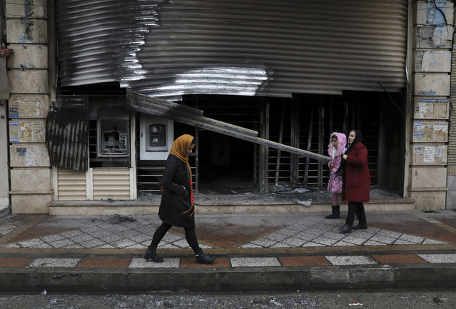 People walk past a bank that was burned during recent protests, in Shahriar, Iran, some 40 kilometers (25 miles) southwest of the capital, Tehran, Wednesday, November 20, 2019. Protests over government-set gasoline prices rising struck at least 100 cities and towns, spiraling into violence that saw banks, stores and police stations attacked and burned. (Photo by Vahid Salemi/AP Photo)