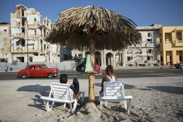 People enjoy an artificial beach at the Malecon sea front created by Cuban Artist Arles del Rio for the 12th Havana Art Biennial, May 21, 2015. (Photo by Alexandre Meneghini/Reuters)