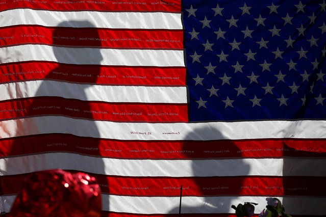 The names of Pulse night club shooting victims are embroidered on a U.S. flag at a makeshift memorial in Orlando, Florida, U.S., June 17, 2016. (Photo by Carlo Allegri/Reuters)