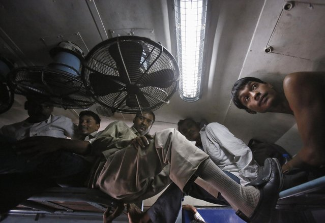 Passengers sit inside a crowded stationary train at a railway station in New Delhi July 8, 2014. (Photo by Anindito Mukherjee/Reuters)