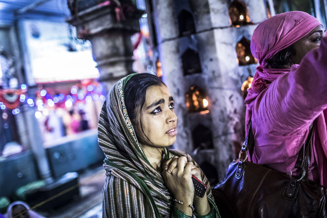 A young Sufi Muslims devoteecries as she clasps her hands in prayer at the 'dargah' or shrine of Sufi saint Muhammad Moin-ud-din Chisti on May 22, 2012 in Ajmer, India
