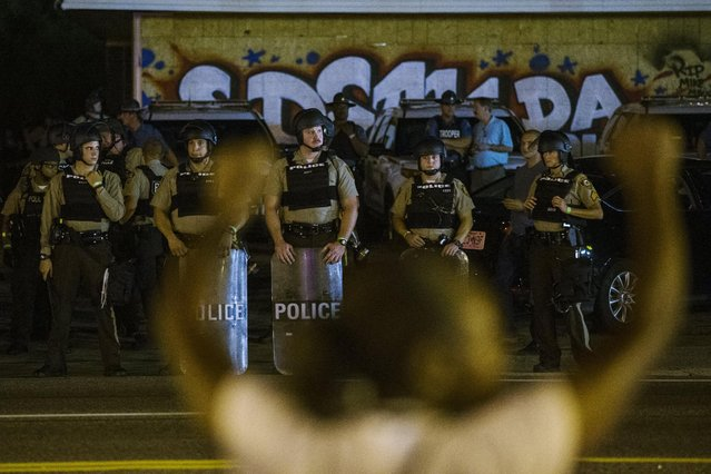 St Louis County police officers watch as anti-police demonstrators march in protest in Ferguson, Missouri August 10, 2015. (Photo by Lucas Jackson/Reuters)