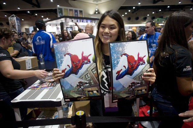 A woman shows free give away memorabilia during the preview night for Comic Con 2017 in San Diego, California, USA, 19 July 2017. (Photo by David Maung/EPA)