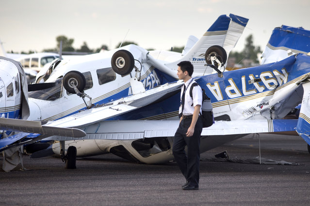 William Wang, a TransPac employee, checks their damaged planes, Wednesday, August 12, 2015, at Chandler Municipal Airport in Chandler, Ariz. At least a dozen small planes were heavily damaged after a monsoon storm swept into the Phoenix area Tuesday night. (Photo by Mark Henle/The Arizona Republic via AP Photo)