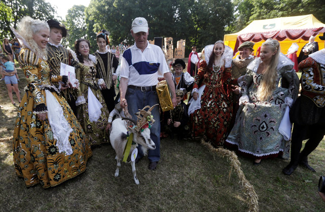 Winner goat Demyte pose for a picture with owner Ferdinandas Petkevicius during the goat beauty pageant in Ramygala, Lithuania, June 26, 2016. (Photo by Ints Kalnins/Reuters)