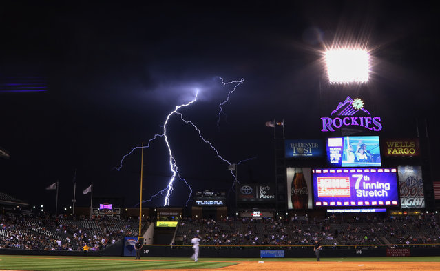 Lightning strikes in the background during the seventh inning of a baseball game between the Colorado Rockies and the San Diego Padres on Monday, July 7, 2014, in Denver. (Photo by Jack Dempsey/AP Photo)