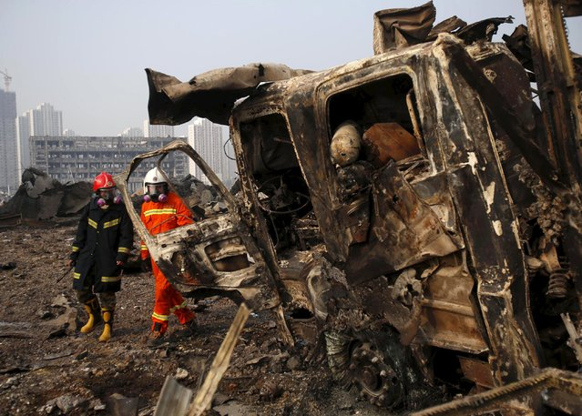Firefighters walk past a damaged truck at the site of Wednesday night's explosions in Binhai new district of Tianjin, China, August 15, 2015. (Photo by Reuters/China Daily)