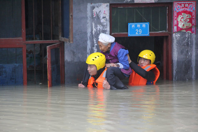 Rescuers save a resident from a flooded building in Chongqing, China, June 28, 2016. (Photo by Reuters/Stringer)
