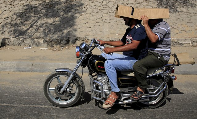 Men cover their heads from the sun while riding on a motorcycle during a hot day in Cairo, Egypt, August 17, 2015. A heatwave killed at least 61 people across Egypt from Sunday to Tuesday and caused nearly 600 people to be admitted to hospital, Egypt's health ministry said on state news agency MENA on Wednesday. (Photo by Amr Abdallah Dalsh/Reuters)