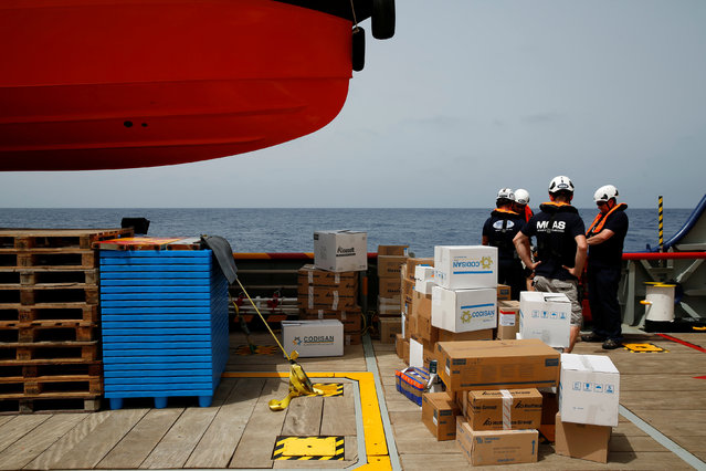 Crew members on the Migrant Offshore Aid Station (MOAS) ship Topaz Responder wait to transfer supplies to the MOAS ship Phoenix in international waters off the coast of Libya, June 18, 2016. (Photo by Darrin Zammit Lupi/Reuters)
