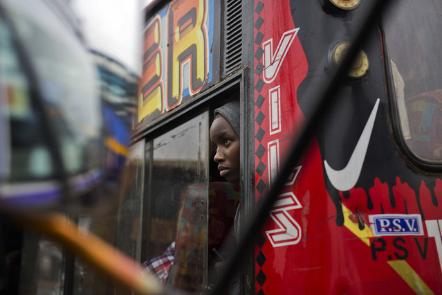 Kenyans wait for their bus to depart in Nairobi, Kenya, Monday August 7, 2017. As the highly competitive presidential election approaches, heavily booked buses are ferrying Kenyans back to their home towns, for some in order to vote where they are registered, but for others it is due to fears of post-election violence in the areas where they live. (Photo by Jerome Delay/AP Photo)